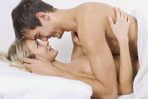 Husband in bed on top of wife